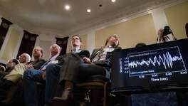 Audience members look at monitors displaying detected data which scientists say is proof of gravitational ripples, Thursday, Feb. 11, 2016, during a news conference at the National Press Club in Washington, just as Albert Einstein predicted a century ago. (AP Photo/Andrew Harnik)