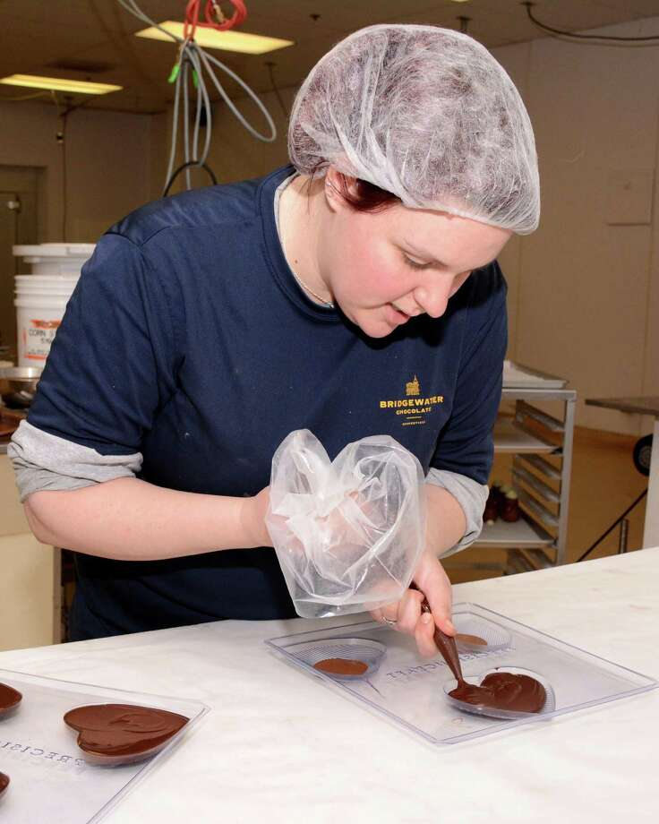 Kelly Burns, 30, from Brookfield fills heart molds with  chocolate preparing for Valentines Day at Bridgewater Chocolates in Brookfield on February 10,2016. Photo: Lisa Weir / For Hearst Connecticut Media / The News-Times Freelance