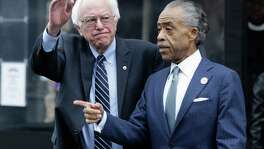Democratic presidential candidate Sen. Bernie Sanders, I-Vt., left, waves to media and supporters after a breakfast meeting with Rev. Al Sharpton at Sylvia's Restaurant, Wednesday, Feb. 10, 2016, in the Harlem neighborhood of New York. Sanders defeated former Secretary of State Hillary Clinton on Tuesday in the New Hampshire primary. (AP Photo/Seth Wenig)