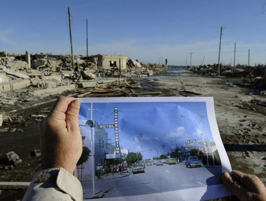 A man compares a picture of Lago Epecuen village taken in the 70's with the current state of the place -- flooded for almost 25 years by the salt water of Epecuen lagoon. Photo: JUAN MABROMATA, AFP/Getty Images