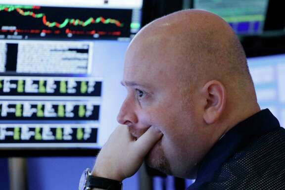 A stock trader works at the New York Stock Exchange on Thursday. The MSCI All-Country World Index sunk into the bear territory Thursday as investors worried once again that weakness in European banks could erupt into a financial crisis.