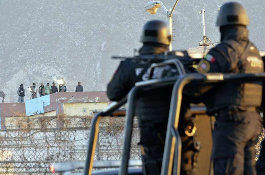 Inmates stand on the rooftop of the Topo Chico prison as police stand guard on the perimeters, after a riot broke out around midnight, in Monterrey, Mexico, Thursday, Feb. 11, 2016. Dozens of inmates were killed and several injured in a brutal fight between two rival factions at the prison in northern Mexico, the state governor said. (AP Photo/Emilio Vazquez) Photo: Emilio Vazquez, STR / AP