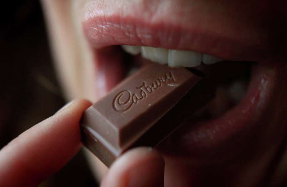 A woman eats a chunk of chocolate from a bar of Cadbury's Dairy Milk chocolate on January 19, 2010 in Bristol, England.  Photo: Matt Cardy, Getty Images / 2010 Getty Images