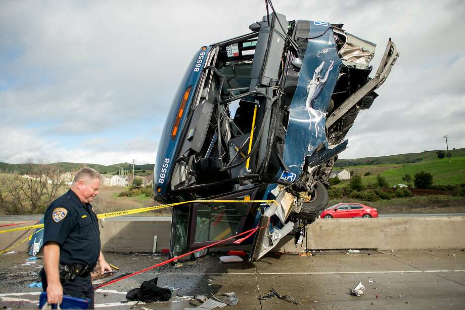 A California Highway Patrol officer moves belongings from a Greyhound bus crash that left two dead and at least eight injured on Tuesday, Jan. 19, 2016, in San Jose, Calif. A Greyhound spokeswoman said the bus, which left Los Angeles Monday night, was carrying 20 passengers in addition to the driver. (AP Photo/Noah Berger) Photo: Noah Berger, Associated Press