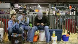 LEFT: Hayden Schroeder, 11 (from left), Blaze Cozart, 11, and Hayden Barker, 16, play on their smartphones at the Stock Show & Rodeo. They were competing in the Junior Breeding Swine Show. Youths from 9 to 18 will show eight breeds of swine in that show.