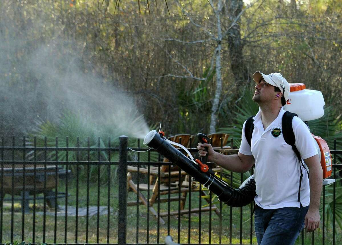 In this Wednesday, Feb. 10, 2016 photo, Darryl Nevins, owner of a Mosquito Joe franchise, sprays a backyard to control mosquitoes in Houston. Pest control companies in Texas are getting an early surge in business because of concerns that mosquitoes bearing the Zika virus will arrive from neighboring Mexico. (AP Photo/Pat Sullivan)