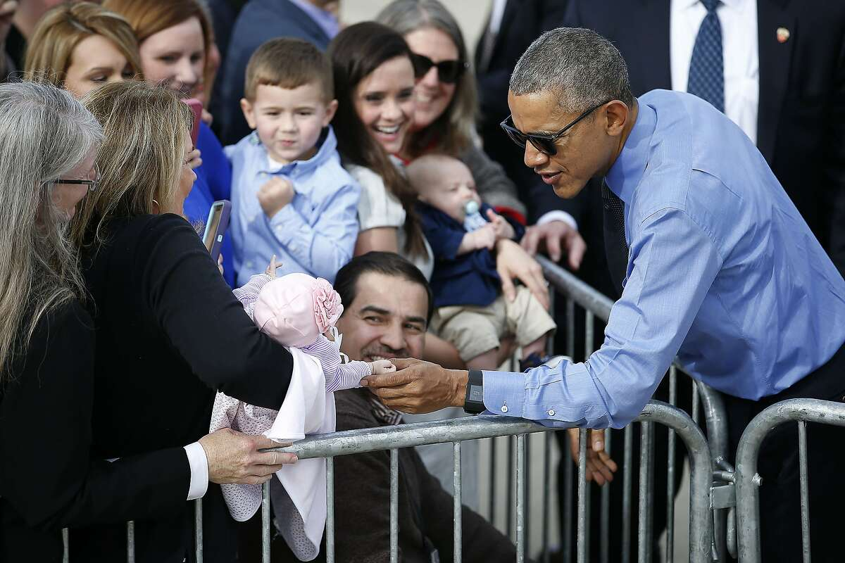 President Barack Obama holds 2 month-old Callie Tate's hand as he meets with the crowd before departing on Air Force One at Moffett Federal Airfield Thursday, Feb. 11, 2016, in Mountain View, Calif. (AP Photo/Tony Avelar)