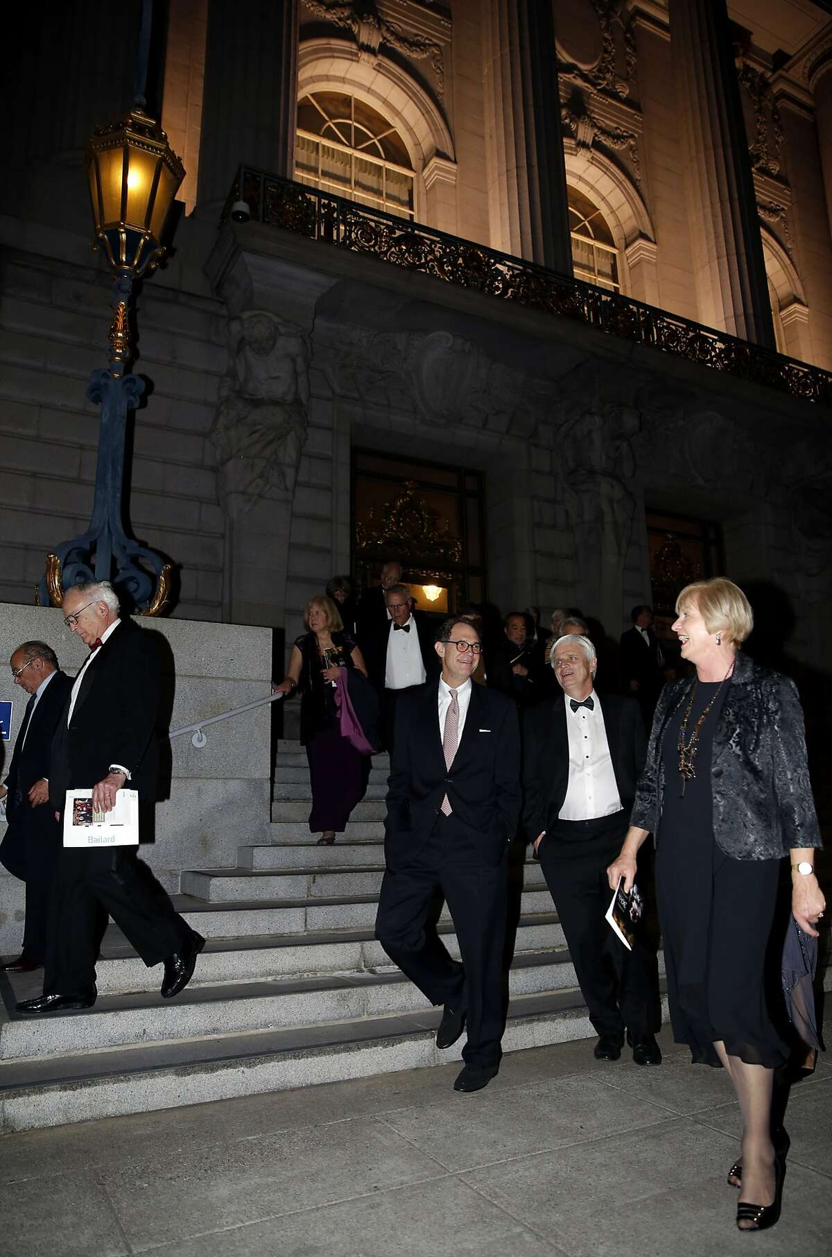 A crowd of well-dressed revelers walk from City Hall to the Herbst Theatre for a concert celebrating the 30th anniversary of the Philharmonia Baroque Orchestra's music director Nicholas McGegan in San Francisco, California, on Thursday, Feb. 11, 2016.