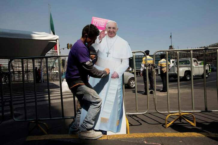 A worker places a life-size cutout of Pope Francis in the Zocalo in downtown Mexico City, Thursday, Feb. 11, 2016. The pontiff  arrives in Mexico on Friday for a week-long visit. (AP Photo/Moises Castillo)