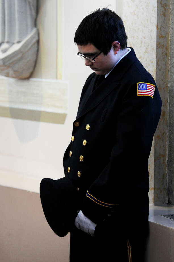 Young Derby Firefighter Luis Oliwa bows his head in silence during the funeral service for former Derby Fire Chief James J. Butler, held at Holy Rosary Church in Ansonia, Conn. Feb. 12, 2016. Butler, 50, a 35-year veteran of the Derby Fire Department, died Sunday shortly after responding to a fire call. Photo: Ned Gerard, Hearst Connecticut Media / Connecticut Post