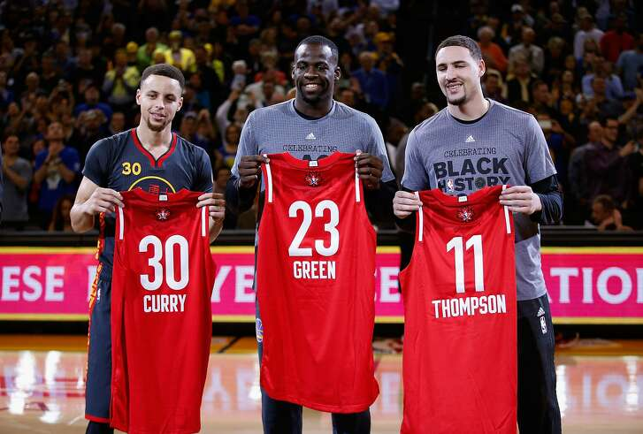Stephen Curry #30, Draymond Green #23 and Klay Thompson #11 of the Golden State Warriors hold up their All-Star jerseys before their game against the Houston Rockets on Feb. 9 at Oracle Arena.