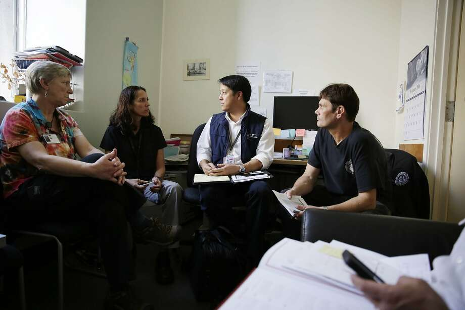 Dr. Clement Yeh (second from right), the medical director for the Fire Department and the 911 dispatch system, meets with staff. Photo: Lea Suzuki, The Chronicle