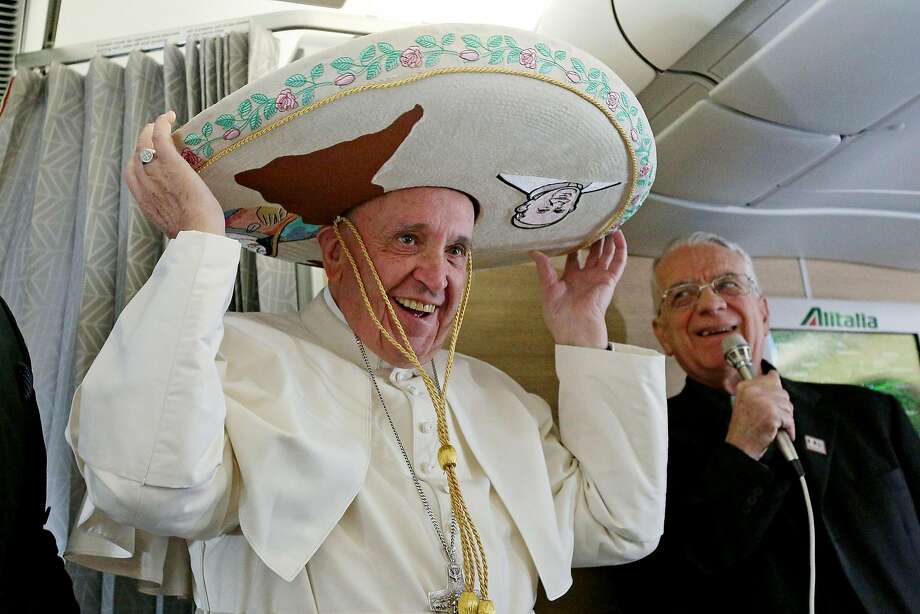 TOPSHOT - Pope Francis wears a traditional Mexican sombrero hat received as a gift by a Mexican journalist on February 12, 2016, aboard the plane to Havana.   Pope Francis headed to Cuba on Friday looking to heal a 1,000-year-old rift in Christianity before embarking on a tour of Mexico dominated by modern day problems of drug-related violence and migration. / AFP / POOL / ALESSANDRO DI MEOALESSANDRO DI MEO/AFP/Getty Images Photo: Alessandro Di Meo, AFP / Getty Images