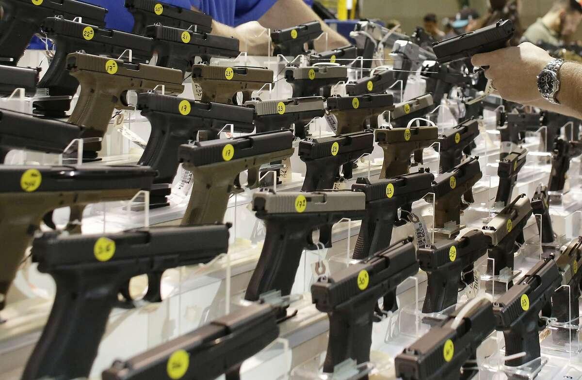 ADVANCE FOR USE SATURDAY, FEB. 6, 2016 AT 8 A.M. EST AND THEREAFTER; THIS STORY MAY NOT BE PUBLISHED, BROADCAST OR POSTED ONLINE BEFORE SATURDAY, FEB. 6, 2016 AT 8 A.M. EST - FILE - A customer looks at a pistol at a vendor's display at a gun show held by Florida Gun Shows in Miami on Saturday, Jan. 9, 2016. States enter data into the national background check system about people who are convicted of crimes that disqualify them from buying guns. That information turns up when licensed dealers conduct background checks and has resulted in more than 120,000 applicants being denied since 1998 for having misdemeanor domestic violence convictions. (AP Photo/Lynne Sladky)