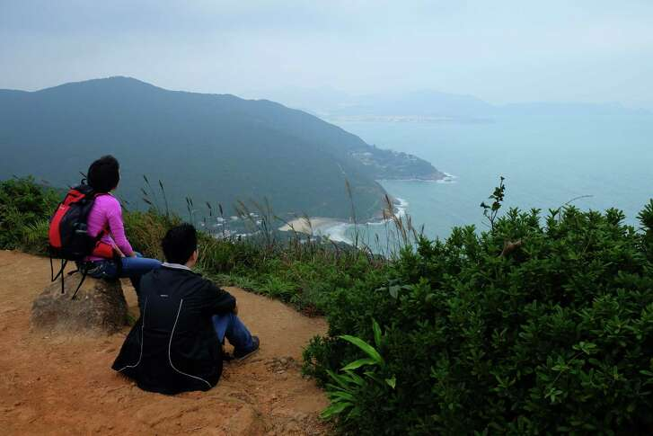 A pair of young hikers pause to enjoy the view from high up on the Dragon's Back Trail in Hong Kong.