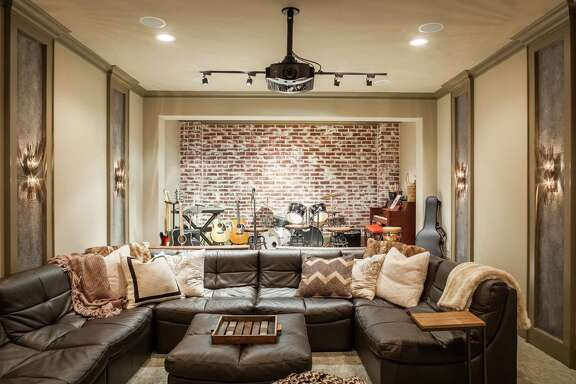 The media room has a stage in back, where the Monsivaiz family and their guests can have singalongs and jam sessions. The back wall is faux brick.