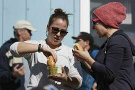 Molly Fogarty (l to r) of New York and Danielle Sycks of Seattle make make bagel sandwiches as they view the Titans of Mavericks on a large screen in front of the Mavericks Surf Shop where Red Bull was showing a live stream of the contest on  Friday, February 12, 2016 in Half Moon Bay, Calif.