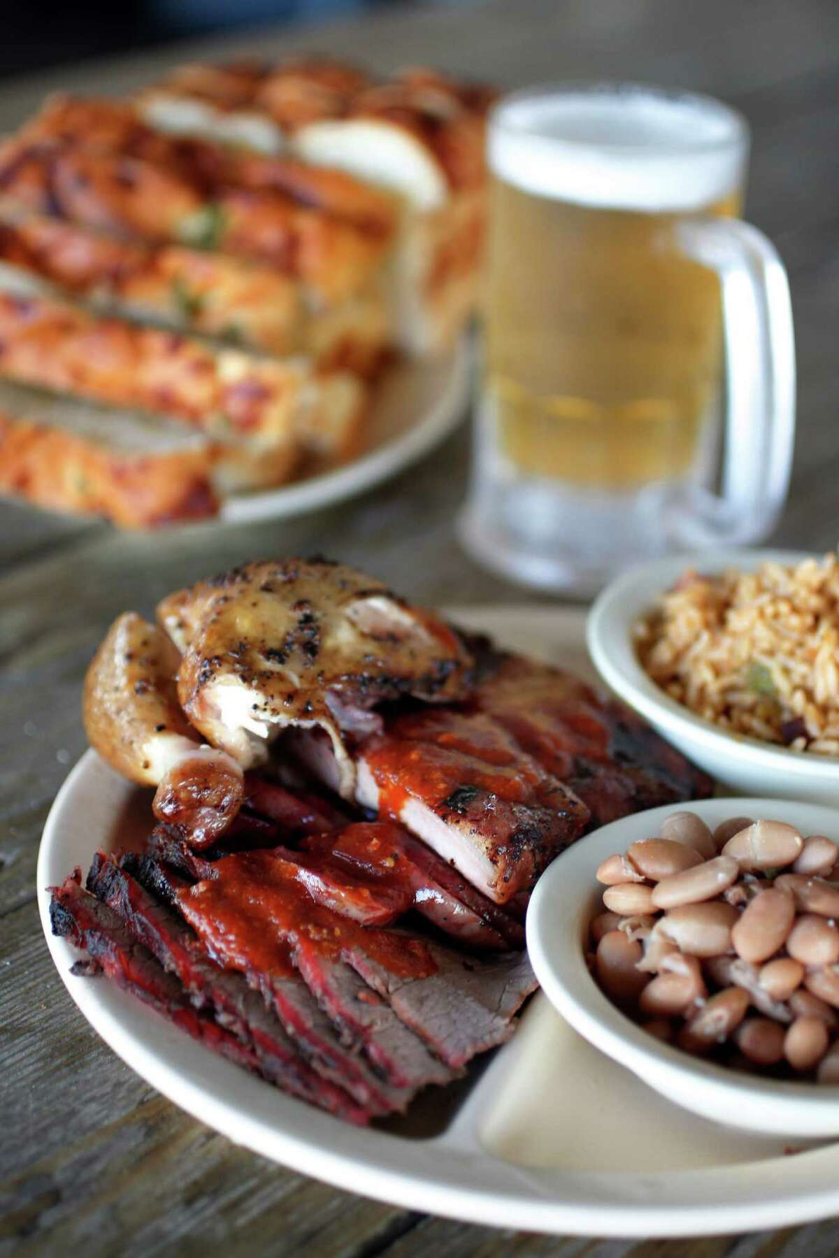 Chicken, Pork Ribs, Beef Brisket, Jambalaya Texana (rice), Jalapeno Pinto Beans, Original Barbeque Sauce and Jalapeno cheese bread served at Goode Co. Barbeque. The company will open two side-by-side restaurants -- Goode Barbecue and Goode Co. Kitchen & Cantina -- in the Woodlands.