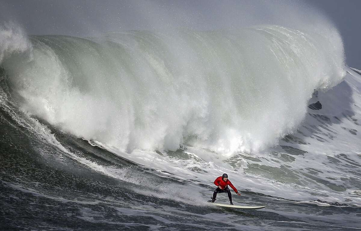 Carlos Burle rides a wive in heat number onein the first round of the Titans of Mavericks competition in Half Moon Bay , Calif., on Friday, February 12, 2016.