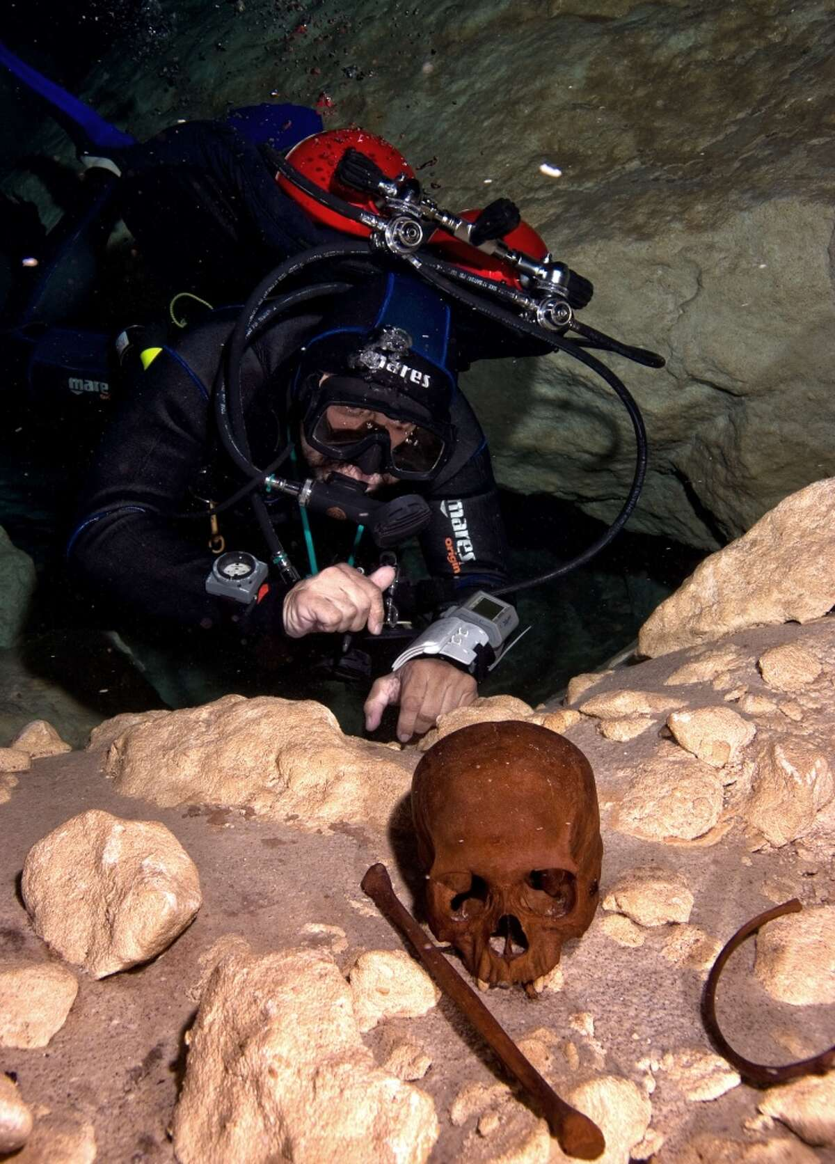 Guillermo de Anda, dives in a cenote filled with Mayan artifacts, inspects sacrificial remains near Homum in Yucatan, Mexico.