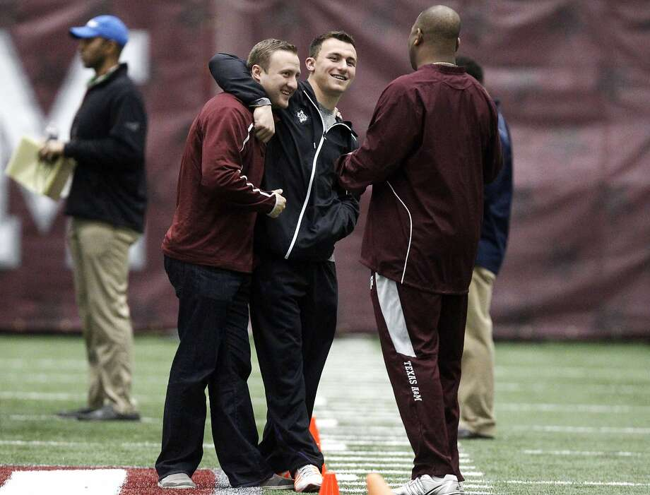 Texas A&M quarterback Johnny Manziel, middle, gives offensive coordinator Jake Spavital a hug during Texas A&M pro day held Wednesday, March 5, 2014, in College Station, Texas. (AP Photo/Patric Schneider) Photo: Patric Schneider, Associated Press