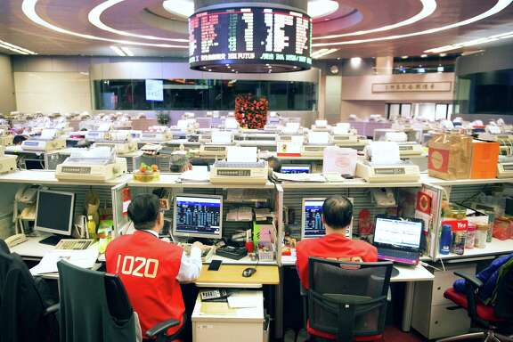 Traders work on the trading floor of the Hong Kong Stock Exchange. Policymakers from Tokyo to Stockholm are embracing the notion of negative interest rates.