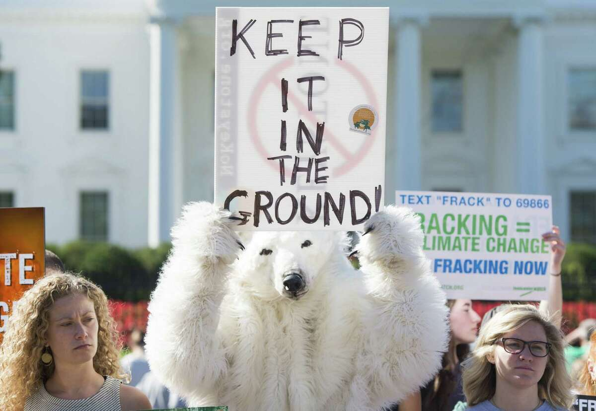 """Environmental activists, including one wearing a polar bear costume, protest the Obama administration's plans to allow new fossil fuel drilling on public lands and oceans, during a demonstration held by the """"Keep it in the Ground"""" coalition in front of the White House in Washington, DC, September 15, 2015. AFP PHOTO / SAUL LOEB (Photo credit should read SAUL LOEB/AFP/Getty Images)"""