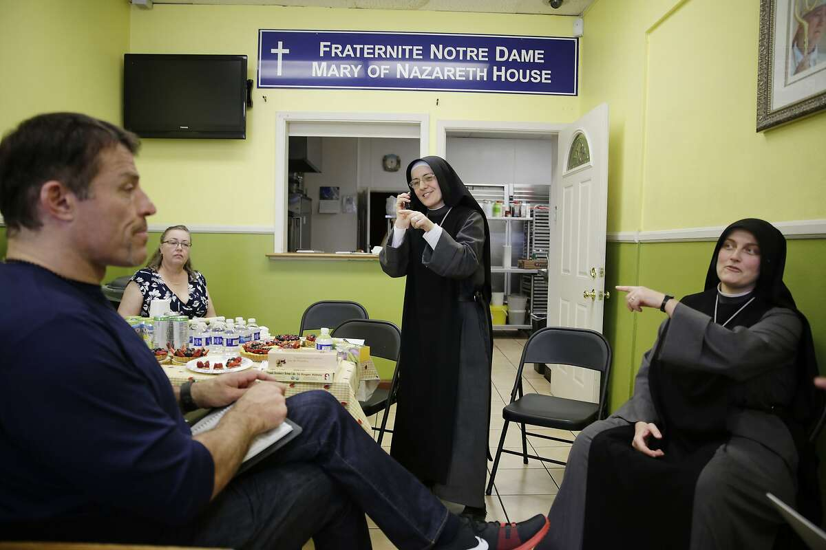 Tony Robbins (left), motivational speaker and author, talks with Sister Mary Benedicte (right) as Sister Mary Valerie (second from right) makes a call to Mother Superior at Fraternite Notre Dame Mother House in Chicago while discussing solutions to their eviction with Robbins at Fraternite Notre Dame Mary of Nazareth Soup Kitchen on Thursday, February 11, 2016 in San Francisco, Calif.