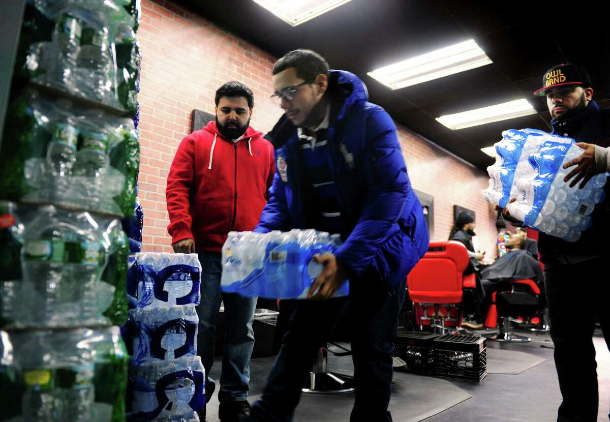 Benny Alicea, center, places a case of donated water with the rest of the water being collected at The Barber Club on Park Avenue in Bridgeport, Conn., on Friday Feb. 12, 2016. At left is volunteer Amir Khan. At right is Ricardo Murillo who spearheaded the water collection. The water which is being doanated at various drop off points around the city, will be taken to Flint, MI to help residents there.