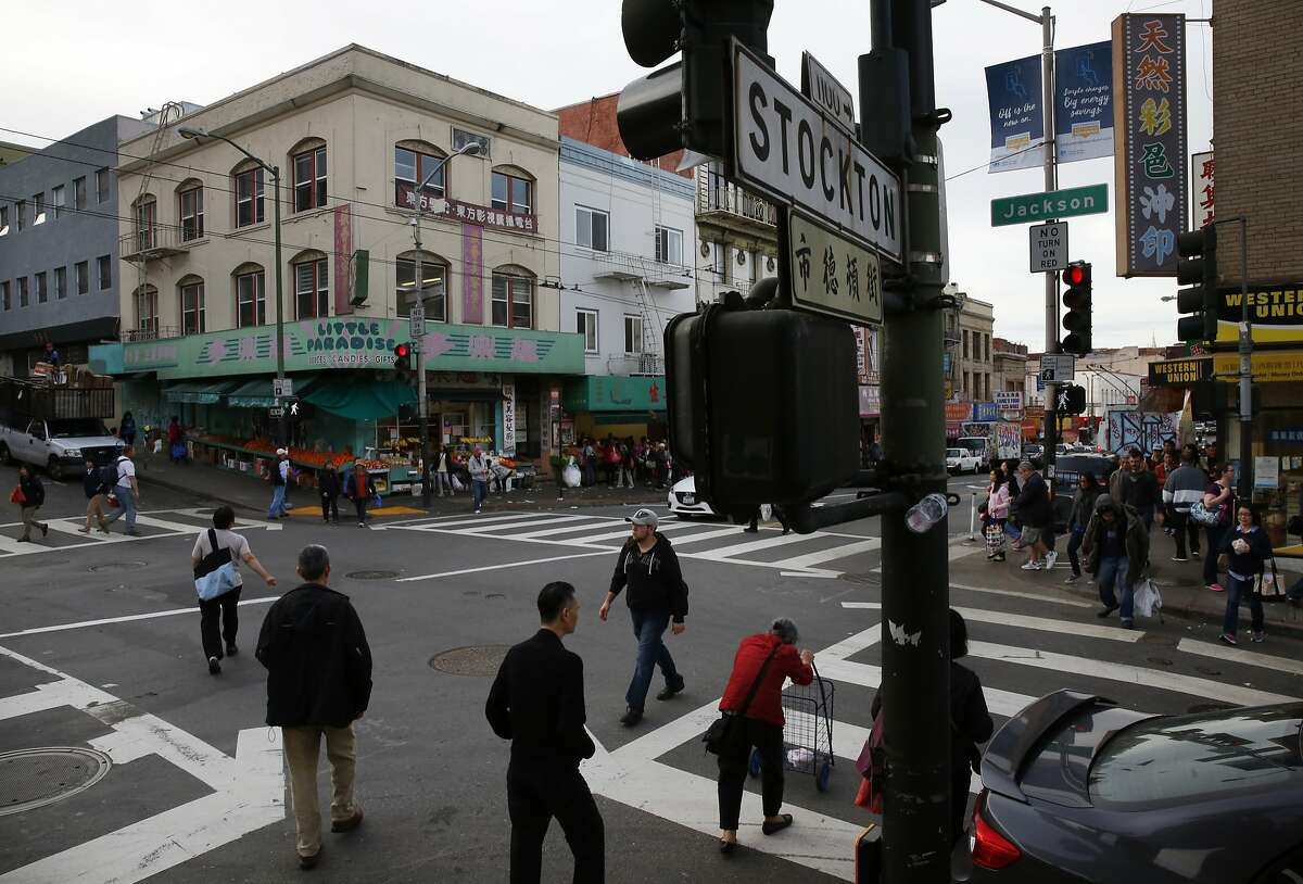 Pedestrians cross Jackson and Stockton Streets at a busy intersection in Chinatown Feb. 12, 2016 in San Francisco, Calif.