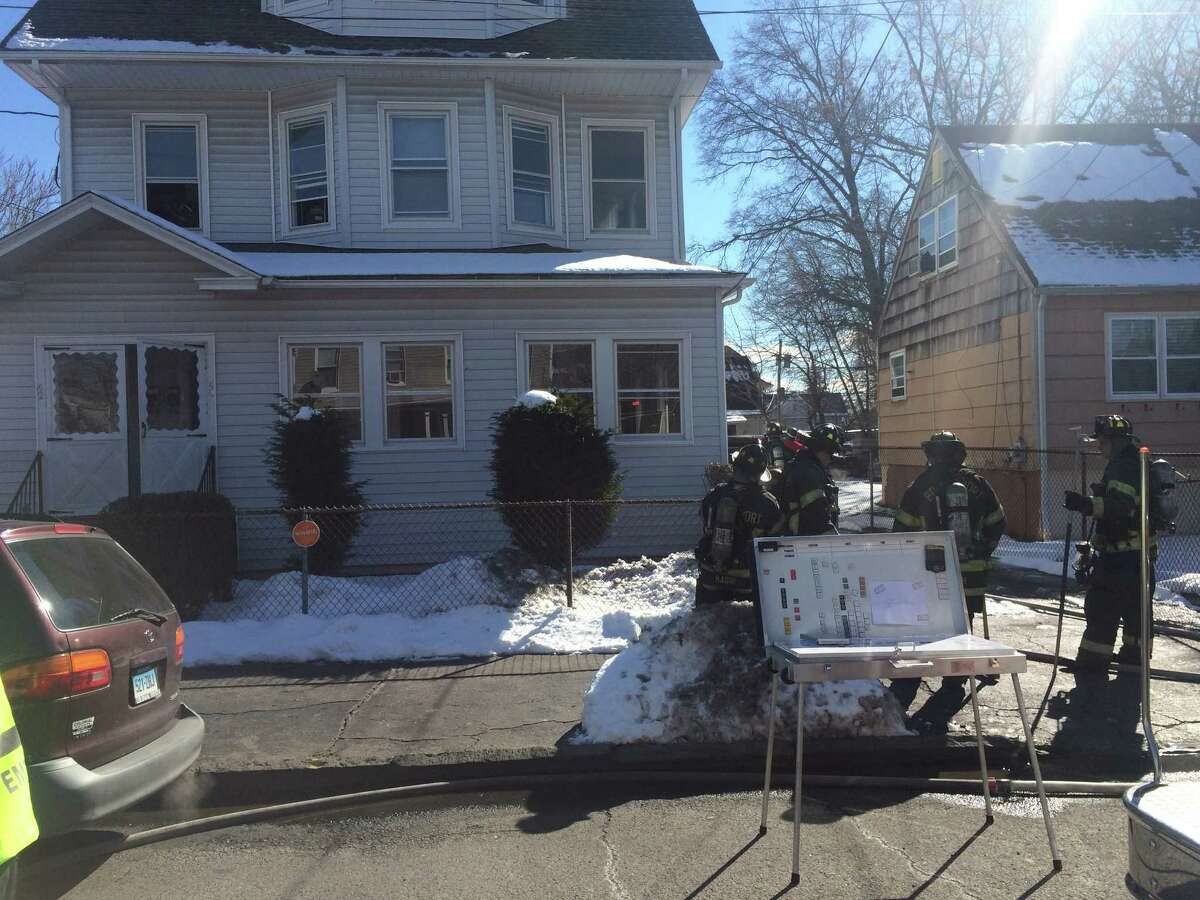Firefighters outside a house at 40-42 Harral Ave. in Bridgeport where a fire left several people homeless on Saturday, Feb. 13, 2016.