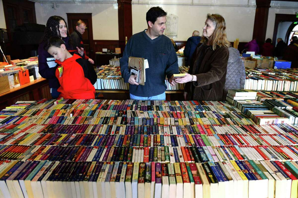Volunteer Claire Ervin, right, hands a book to Brian Solomon, of Bridgeport, at the Mid-Winter Book Sale at the Pequot Library in Southport, Conn. on Saturday Feb. 13, 2016. At left is Brian's children Jack, 11, and Layla, 14. The book sale continues Sunday from 9 a.m. to 5 p.m. Admission is free and all proceeds support the library's annual programs for adults and children.