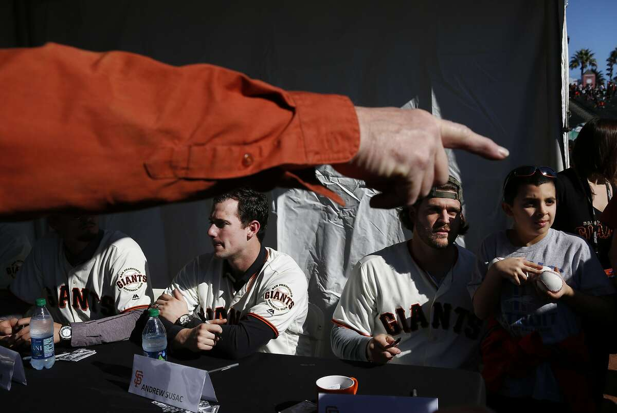 Spencer Cherrin, 9, from Detroit, right, poses for a photograph with Josh Osich while Andrew Susac sits at left as they sign autographs during the annual Giants Fan Fest at AT&T Park Saturday, Feb. 13, 2016 in San Francisco, Calif. Thousands of fans came to the park to see their favorite players, eat food, explore the field and the clubhouse.