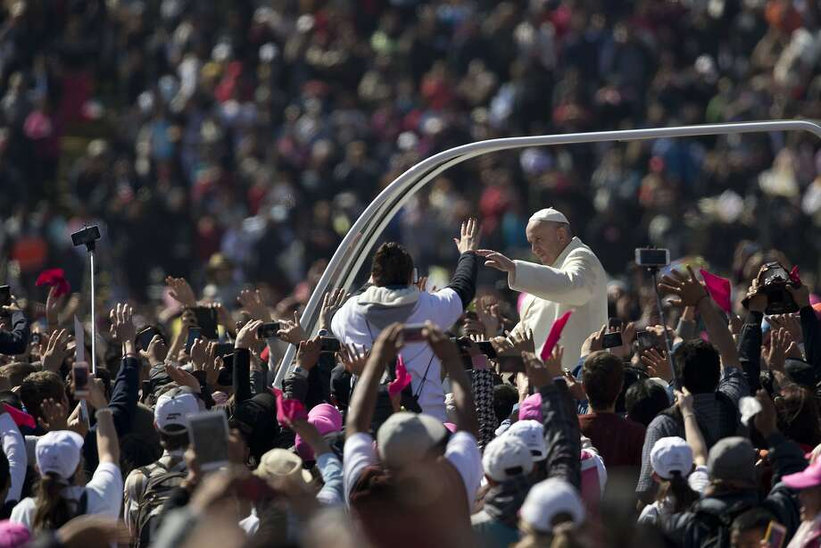 Pope Francis greets the crowd in Mexico City's main square, the Zocalo. Francis told church leaders known for their deference to Mexico's powerful not to hide behind their own privilege. Photo: Moises Castillo, Associated Press