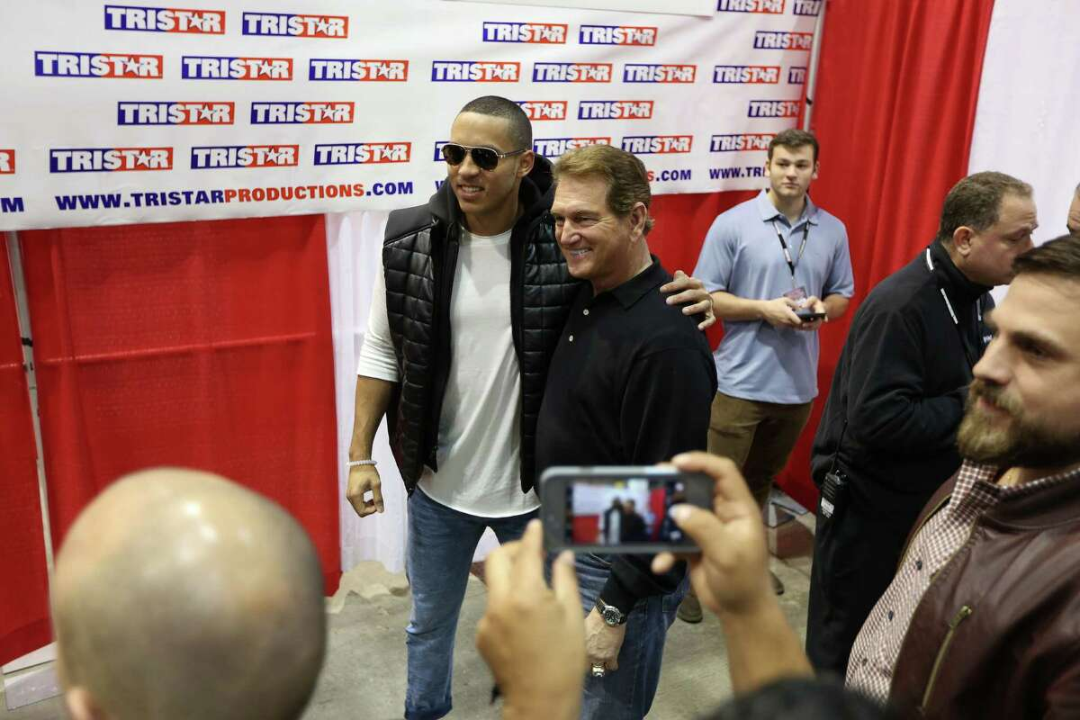 NFL great Joe Theismann has his photo taken with Astros shortstop Carlos Correa's as they signed autographs at the TriStar Show at NRG Arena Saturday, Feb. 13, 2016, in Houston.