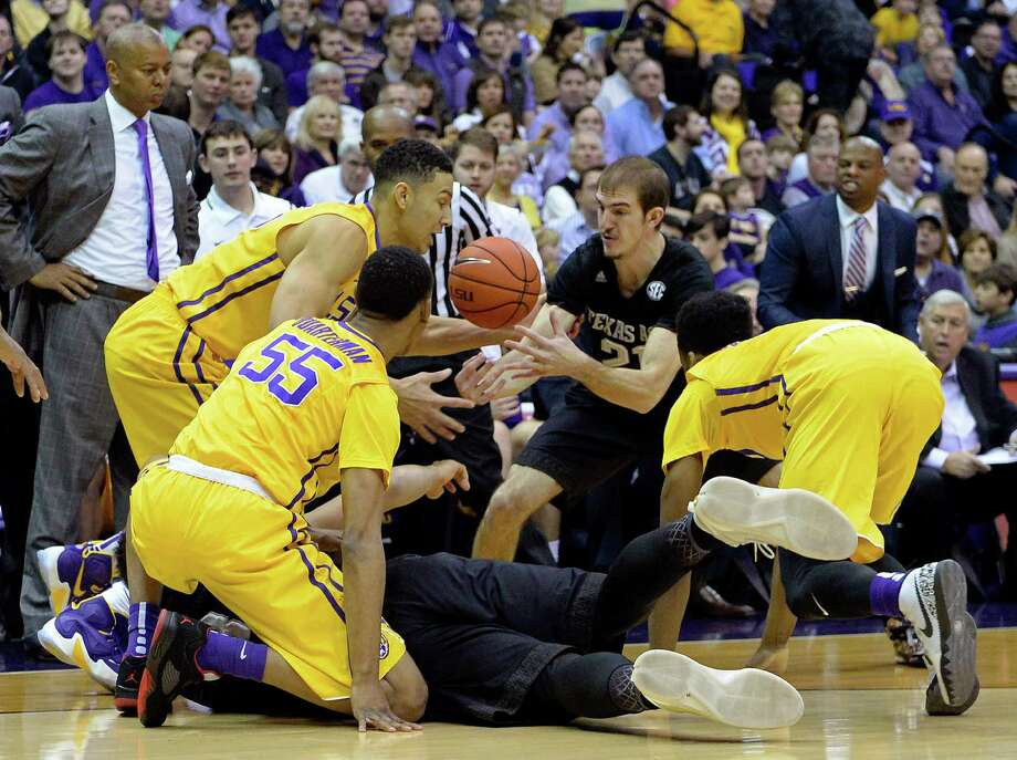 As LSU head coach Johnny Jones, standing left, watches, LSU guard Tim Quarterman (55), LSU forward Ben Simmons, second from left, Texas A&M guard Alex Caruso (21), Texas A&M center Tyler Davis (34), on floor, and LSU guard Antonio Blakeney (2) go after a loose ball in the first half of an NCAA college basketball game in Baton Rouge, La., Saturday, Feb. 13, 2016. (AP Photo/Bill Feig) Photo: BILL FEIG, FRE / Associated Press / FR44286 AP