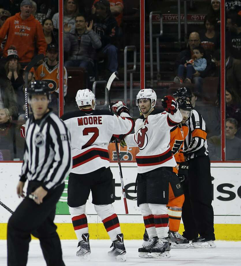 Fans in Philadelphia give New Jersey's Adam Henrique (right) the silent treatment as he celebrates with John Moore (2) after his game-winning goal during overtime. Photo: Matt Slocum, Associated Press