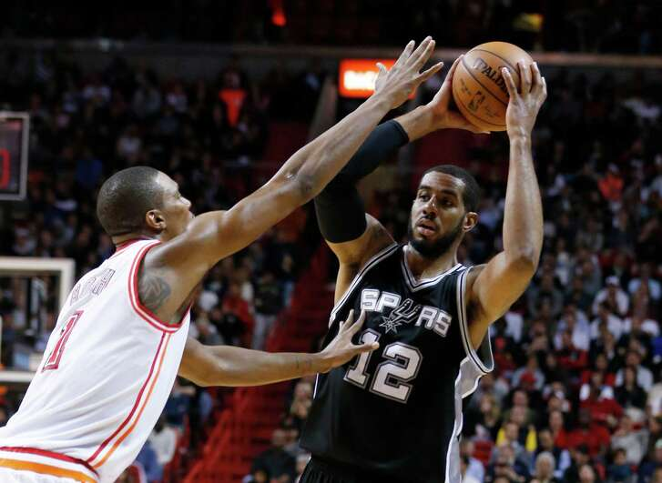 San Antonio Spurs forward LaMarcus Aldridge (12) looks for an open teammate past Miami Heat forward Chris Bosh (1) during the second half of an NBA basketball game, Tuesday, Feb. 9, 2016, in Miami. The Spurs defeated the Heat 119-101. (AP Photo/Wilfredo Lee)