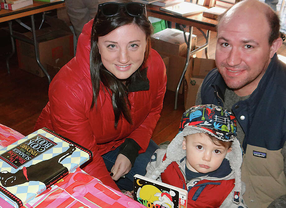 Fairfielders Jessica and Mike Gavejian, with 21-month-old son, Cassius, browsed through thousands of titles on offer at the Pequot Library's Mid-Winter Book Sale. Photo: Fairfield Citizen / Mike Lauterborn / Fairfield Citizen