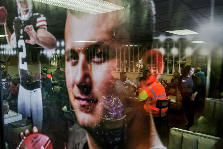 Diners at Loggins Restaurant in Tyler are reflected in a poster of Johnny Manziel, whose grandfather owns the eatery.