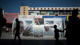 Passersby walk near a Pope Francis display in the center of town, Friday, February 12, 2016, in Juarez, Mexico. Photo by Ivan Pierre Aguirre for San Antonio Express-News