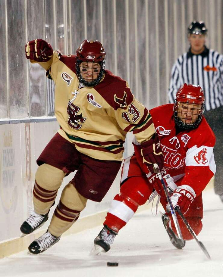 Boston College's Cam Atkinson (13) and Boston University's Luke Popko (26) ight for the puck on January 8 during the Sun Life Frozen Fenway Hockey Game at  Fenway Park in Boston. Atkinson and the Eagles play MIami, Ohio in the Frozen Four Thursday. Photo: Elsa, Getty Images / 2010 Getty Images