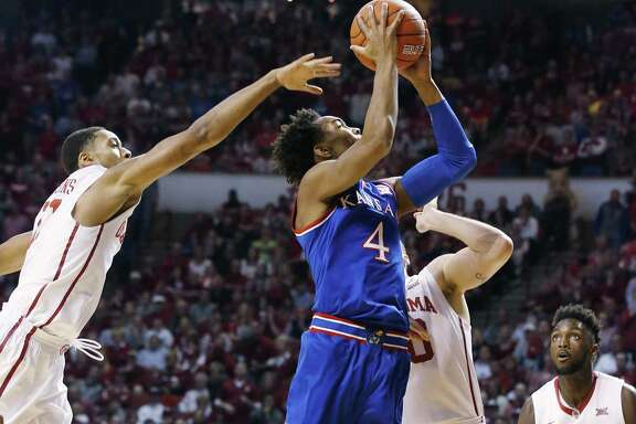 Kansas guard Devonte' Graham was too much for Oklahoma's Isaiah Cousins, left, Ryan Spangler, center, and forward Khadeem Lattin to handle Saturday, scoring a career-high 27 points in the Jayhawks' victory.