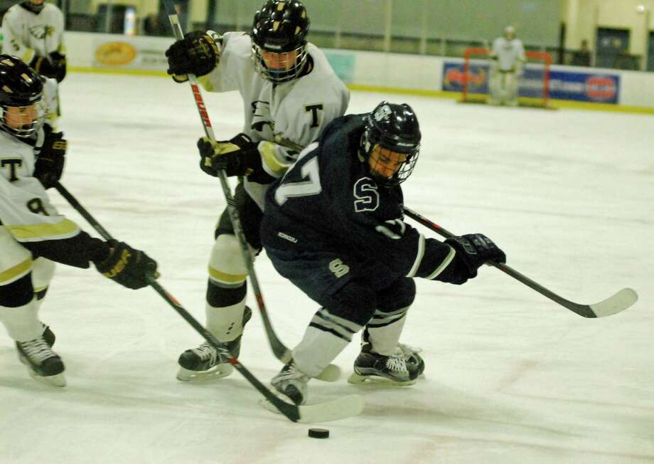 Staples-Weston-Shelton's RJ Gupta, right, is guarded by a pair of Trumbull players during a boys hockey game on Saturday, February 13th, 2016. Photo: Ryan Lacey/Staff Photo / Westport News Contributed