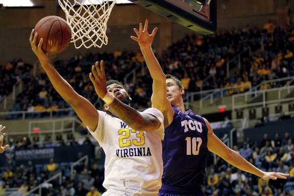 West Virginia's Esa Ahmad, left, lays in a shot against TCU's Vladimir Brodziansky for two of his career-high 14 points in the Mountaineers' victory.