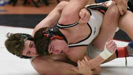 Payton Turbyfill, left, of Reagan High School, battles Mark Lozano of Churchill. Turbyfill improved to 47-0.