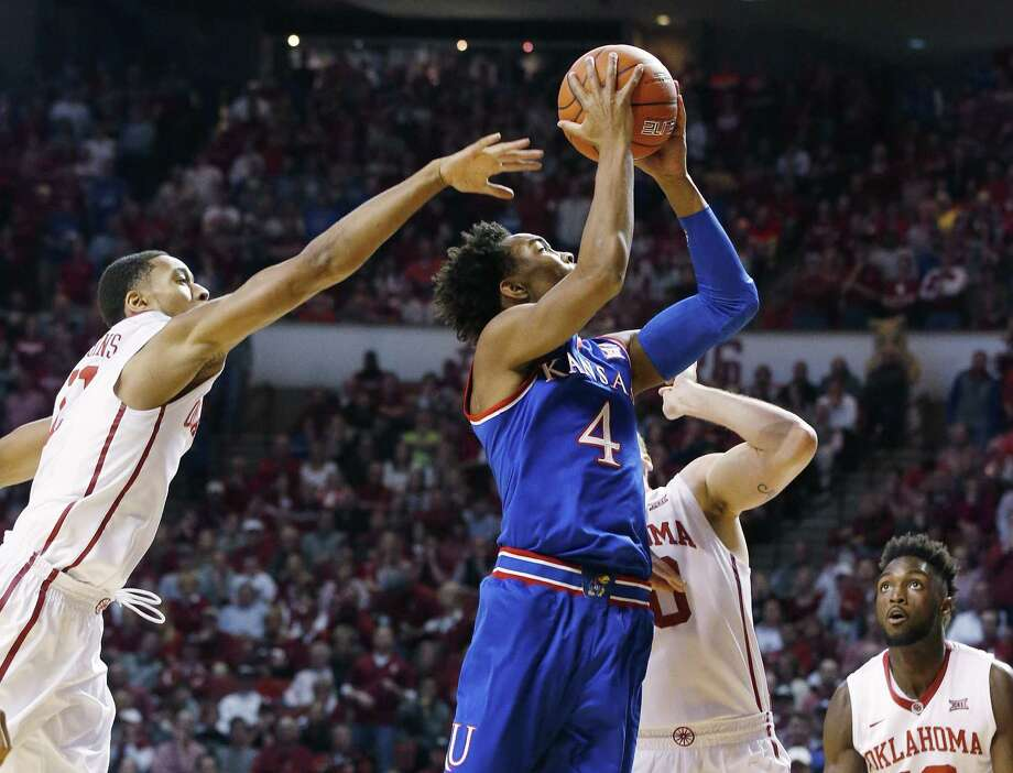 Kansas guard Devonte' Graham (4) shoots between Oklahoma guard Isaiah Cousins, left, forward Ryan Spangler, center, and forward Khadeem Lattin, right, in the first half of an NCAA college basketball game in Norman, Okla., Saturday, Feb. 13, 2016. (AP Photo/Sue Ogrocki) ORG XMIT: OKSO106 Photo: Sue Ogrocki / AP