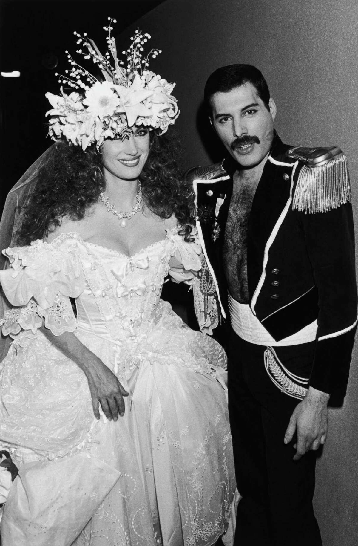 English actress Jane Seymour in a white ballgown with singer Freddie Mercury (1946 - 1991) of British rock group Queen in a military-style dress uniform during Fashion Aid, 6th November 1985.