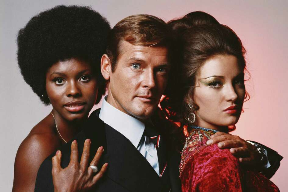 English actor Roger Moore in his role as James Bond in Guy Hamilton's film 'Live And Let Die', circa 1973, with co-stars Gloria Hendry (left), who plays Rosie Carver, and Jane Seymour, who plays Solitaire.