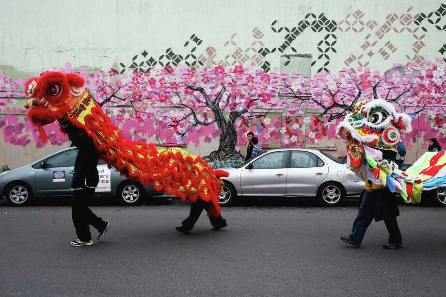 The lion dancers from Northwest Kung Fu and Fitness and Ying Yong Tong make their way through the International District, blessing businesses and ringing in the Year of the Monkey during the annual Lunar New Year Celebration Saturday, February 13, 2016, in Seattle, Washington. The day-long celebration includes traditional dragon and lion dances, Japanese Taiko Drumming, martial arts, delicious foods and crafting. Photo: GENNA MARTIN, SEATTLEPI.COM / SEATTLEPI.COM
